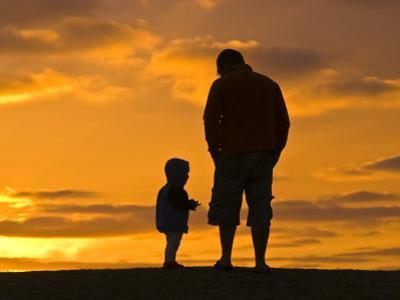 Father and His Baby Son Watch the Sunrise from a Coastal Hilltop by Jason Edwards