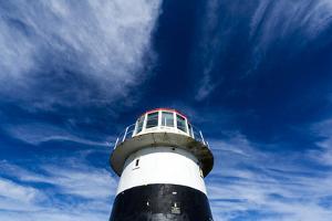 High Winds Swirl Clouds around the Pillar of an Antique Lighthouse by Jason Edwards