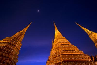 Moonrise over the prang of the Phra Maha Chedi rising into night sky. by Jason Edwards