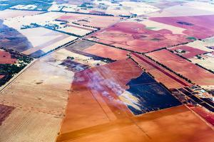 Smoke Rises from Agricultural Crops Being Burned on a Vast Plain of Arid Farmland by Jason Edwards