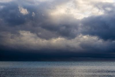 Storm Clouds Reflected in a Calm Tropical Ocean at Dawn