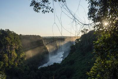 Sun Rays Pierce a Misty Gorge Above the Zambezi River by Jason Edwards