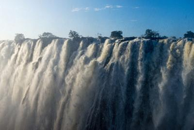 Sunlight Catches the Cascading Pillars of the Zambezi River as They Pour over Victoria Falls by Jason Edwards