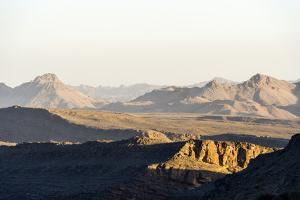 Sunset Catches Jagged Mountain Peaks and Valleys in a Desert by Jason Edwards