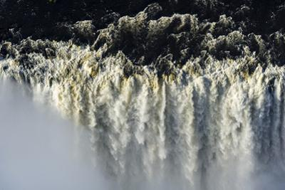 The Flooded Waters of the Zambezi River Cascade in a Curtain across the Face of Victoria Falls by Jason Edwards