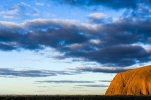 The Last Sunrays of Sunset Touch the Sandstone Massive of Uluru on the Desert Plain by Jason Edwards