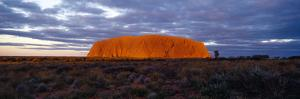 The Last Sunrays of Sunset Touch the Sandstone Massive of Uluru on the Desert Plain by Jason Edwards