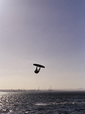 The Silhouette of a Person Kite Surfing, in a Choppy Windswept Bay, Australia by Jason Edwards