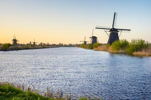 Historic Dutch windmills on the polders at sunset, Kinderdijk, UNESCO World Heritage Site, South Ho by Jason Langley