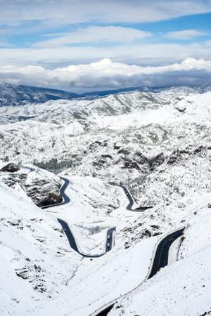 Winding road through Tizi N'Tichka pass in the Atlas Mountains during winter snow, Al Haouz Provinc by Jason Langley
