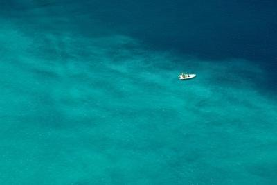 A Boat Floats In The Sea Off The Coast Of Italy