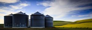A Photographer Is Hidden Among The Grain Sylos Of A Farm In The Palouse Of Washington State by Jay Goodrich