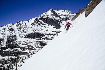 Skiing A Ridgline In The Backcountry Of Glacier National Park