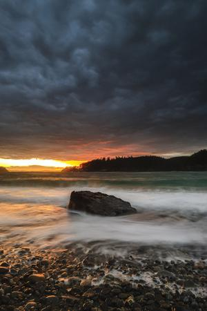 The Sun Sets Through the Clouds at Deception Pass State Park in Washington