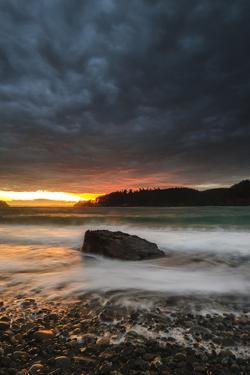 The Sun Sets Through the Clouds at Deception Pass State Park in Washington by Jay Goodrich