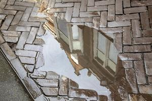 Europe, Netherlands, The Hague. Buildings reflected in sidewalk rain puddle. by Jaynes Gallery
