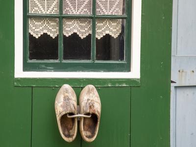 Europe, Netherlands, Zaanse Schans. Wooden shoes on wall outside village house.
