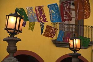 Mexico, San Miguel de Allende. Lantern with string of flags on them. by Jaynes Gallery