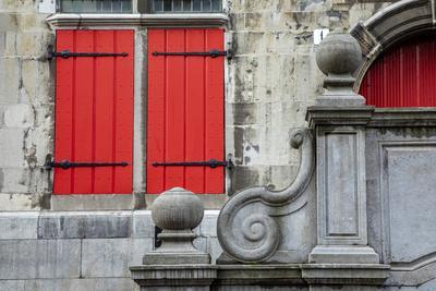 Netherlands, The Hague. Red shuttered window and stone scroll on 16th century Old City Hall.