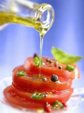 Spiced Tomatoes Being Drizzled with Olive Oil by Jean-Paul Chassenet