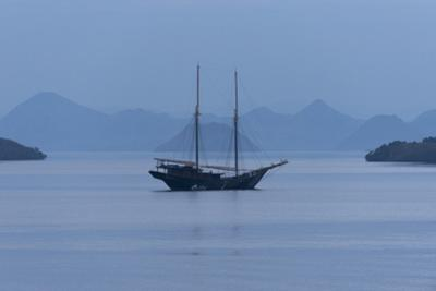 A Pinisi Sailing Vessel Off the Coast of Rinca Island, Komodo National Park, Indonesia by Jeff Mauritzen