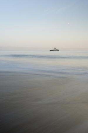 A Ship at Sunrise Along the Coast of Santiago Island, Galapagos Islands, Ecuador by Jeff Mauritzen