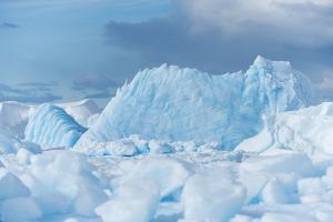 Blue Iceberg Floats Amidst Sea Ice in Fournier Bay, Antarctica by Jeff Mauritzen
