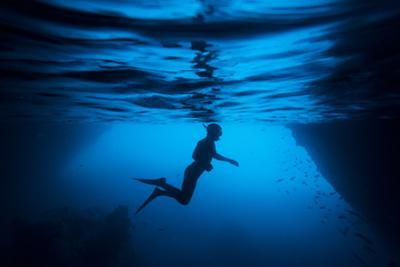 Silhouette of a Swimmer Snorkeling Near a Cave on Santiago Island in the Galapagos by Jeff Mauritzen