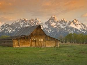 Log Barn in Meadow near Mountain Range by Jeff Vanuga