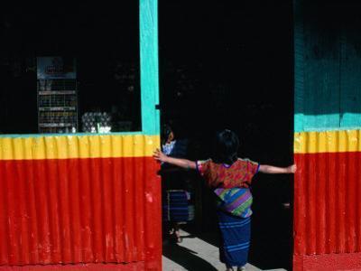 Girl Standing in Market Doorway, Santa Maria De Jesus, Guatemala by Jeffrey Becom
