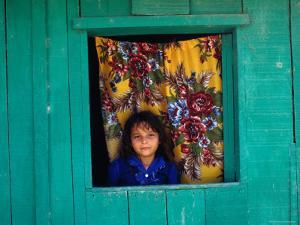 Little Girl in the Window of Her Brightly Painted House, Ciudad Melchor de Mencos, Guatemala by Jeffrey Becom