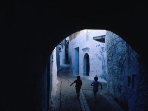 Two Boys Running Through Kasbah, Chefchaouen, Morocco by Jeffrey Becom