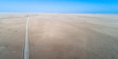 Straight road in the middle of a remote desert landscape. by Jeffrey Kerby
