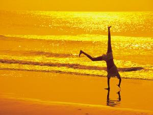 Girl Doing Cartwheels on Beach at Sunset by Jennifer Broadus