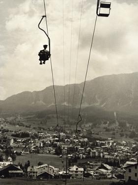 Man Riding Chair Lift Above Town by Jerry Cooke