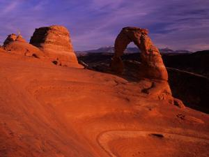 Hikers View Delicate Arch at Sunset, Utah, USA by Jerry Ginsberg