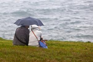 A Couple Seeks Protection from the Rain Underneath an Umbrella at the Cliffs of Moher by Jill Schneider