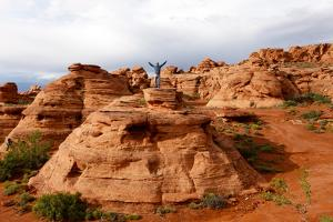 A Man Standing on Top of a Rock Formation in Saint George, Utah, USA by Jill Schneider