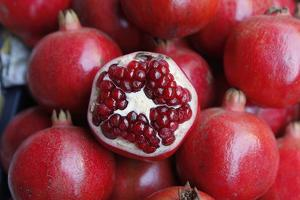 Close Up of Pomegranates for Sale at a Local Market in Mumbai by Jill Schneider