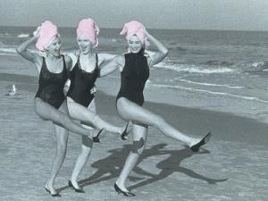 Three Women on Beach with Pink Towels on Head by Jim McGuire