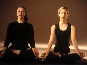 Two Women in Traditional Yoga Position by Jim McGuire