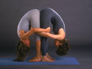 Women in Yoga Posture Together by Jim McGuire