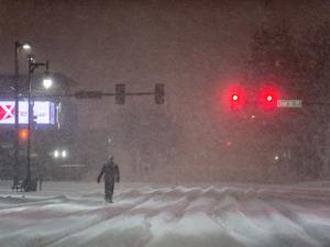 A Man Walking to Work Waits for a Red Light During a Predawn Snowstorm by Jim Reed