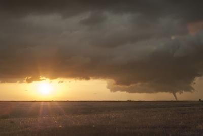 A Tornado Moves across Farmland at Sunset