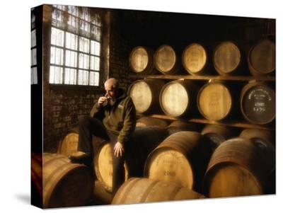 A Worker Tastes Whisky in a Distillery Surrounded by Aging Barrels by Jim Richardson