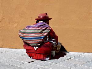 Old Woman with Sling Crouches on Sidewalk, Cusco, Peru by Jim Zuckerman