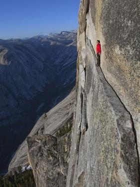 A climber walks a 40-foot-long sliver of granite on Half Dome, named the Thank God Ledge. by Jimmy Chin