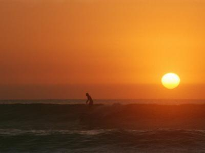 A Man Surfs as the Sun Sets on the Pacific Ocean, Baja, Mexico by Jimmy Chin