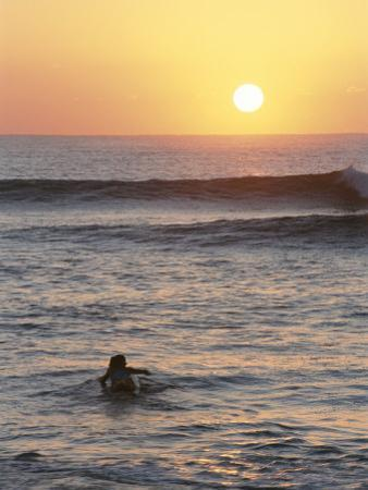 A Woman Paddles out to Sea for Sunset Surfing by Jimmy Chin