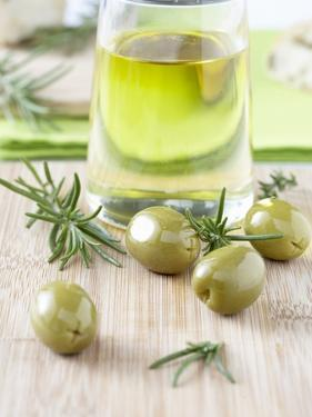 Olive Oil, Green Olives and Rosemary on Chopping Board by Jo Kirchherr